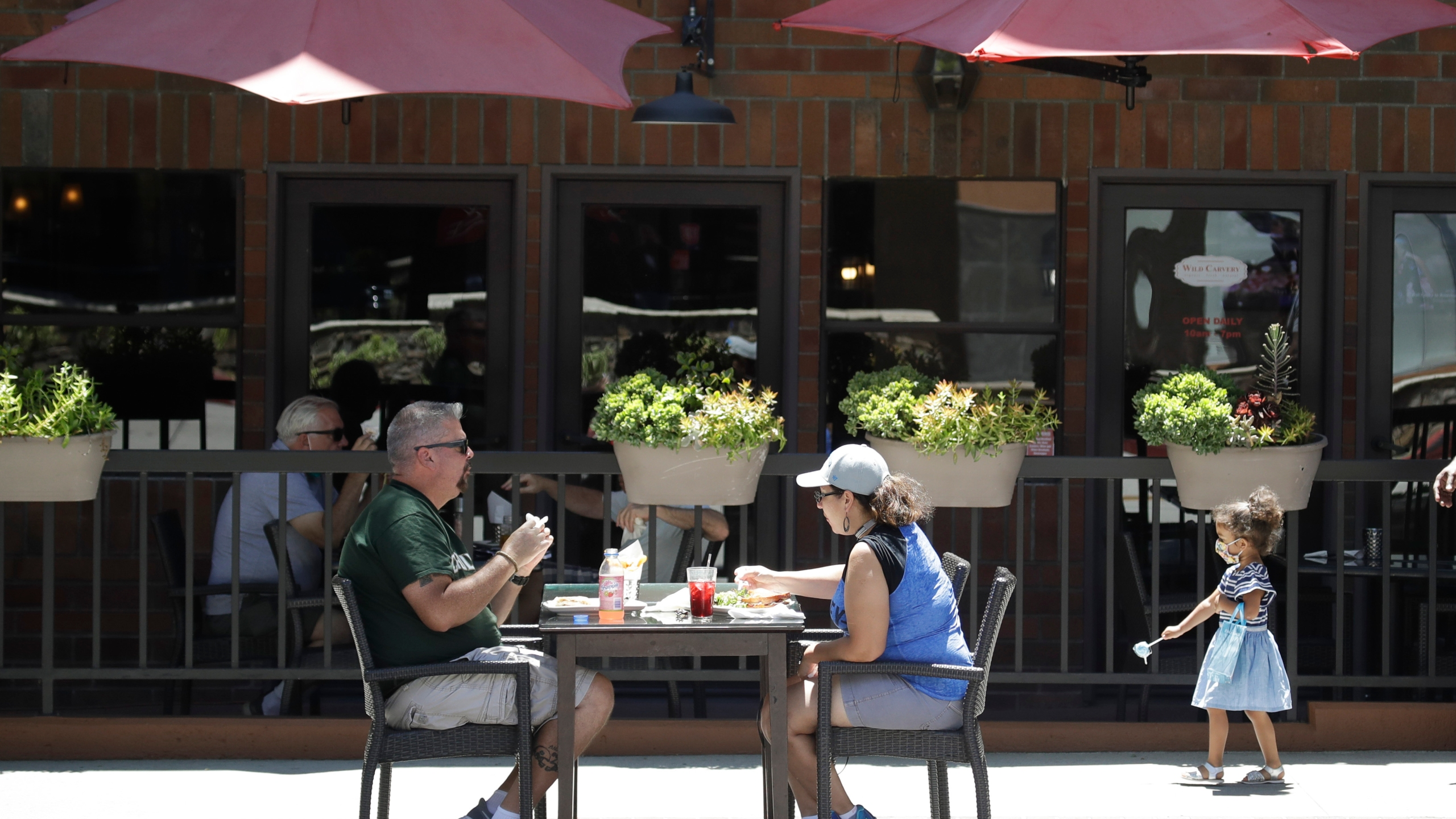 In this July 18, 2020 file photo, patrons eat at a table set up on a sidewalk in Burbank, Calif. (Marcio Jose Sanchez/AP)