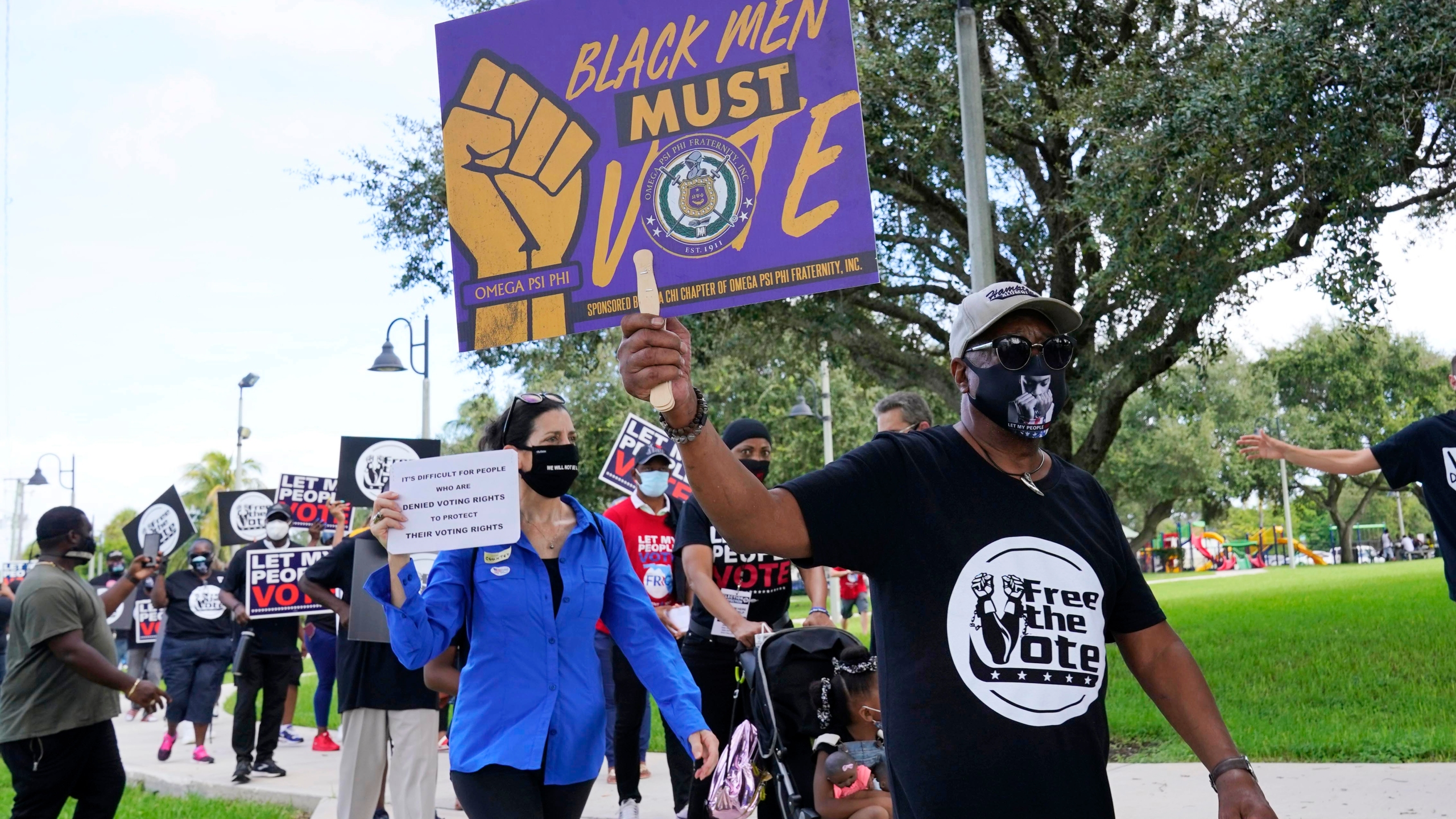 Supporters of restoring Florida felons' voting rights march to an early voting precinct, Saturday, Oct. 24, 2020, in Fort Lauderdale, Fla. (AP Photo/Marta Lavandier)