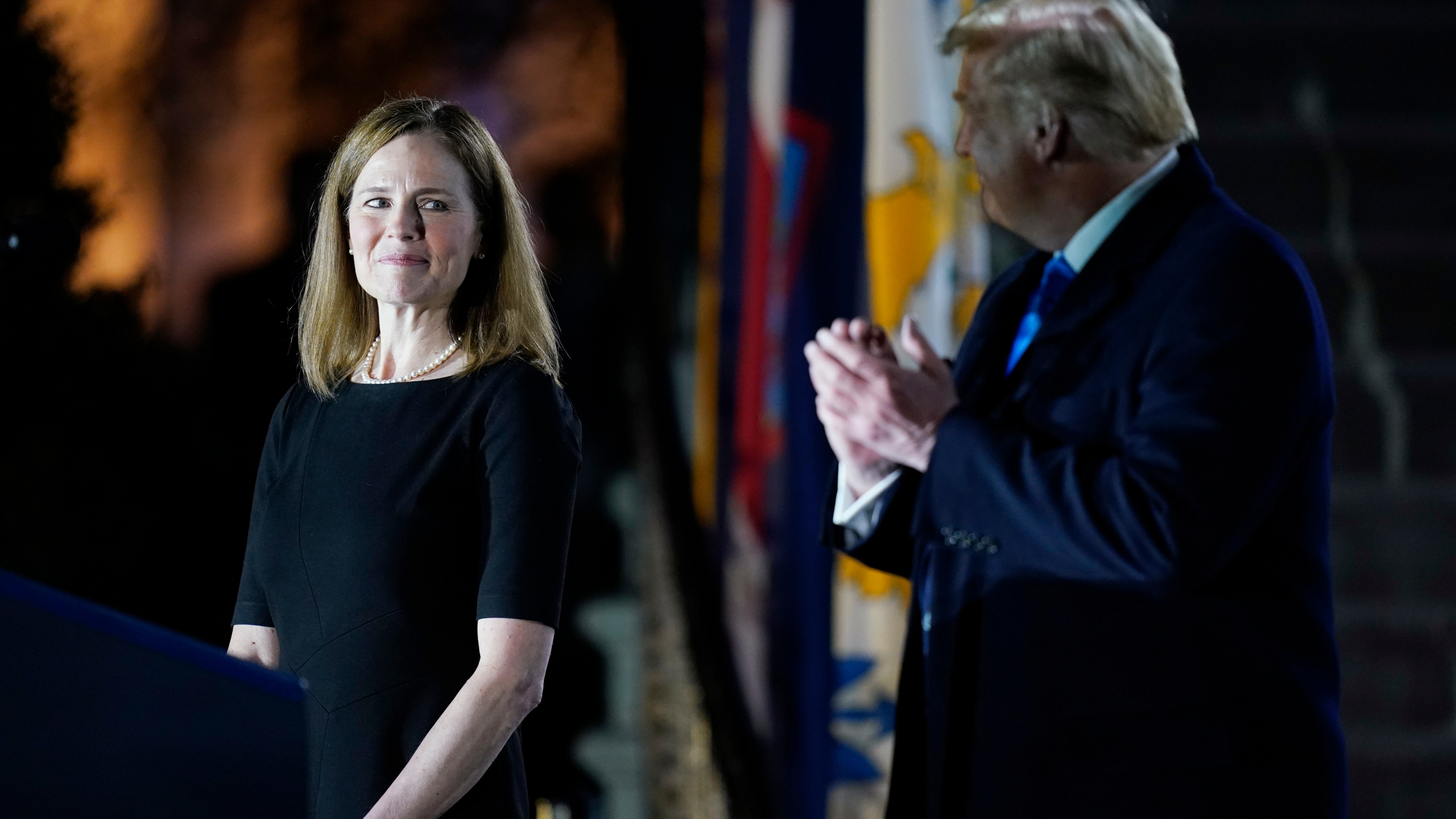 President Donald Trump looks toward Amy Coney Barrett, before Supreme Court Justice Clarence Thomas administers the Constitutional Oath to her on the South Lawn of the White House on Oct. 26, 2020, after Barrett was confirmed by the Senate earlier in the evening. (Patrick Semansky / Associated Press)