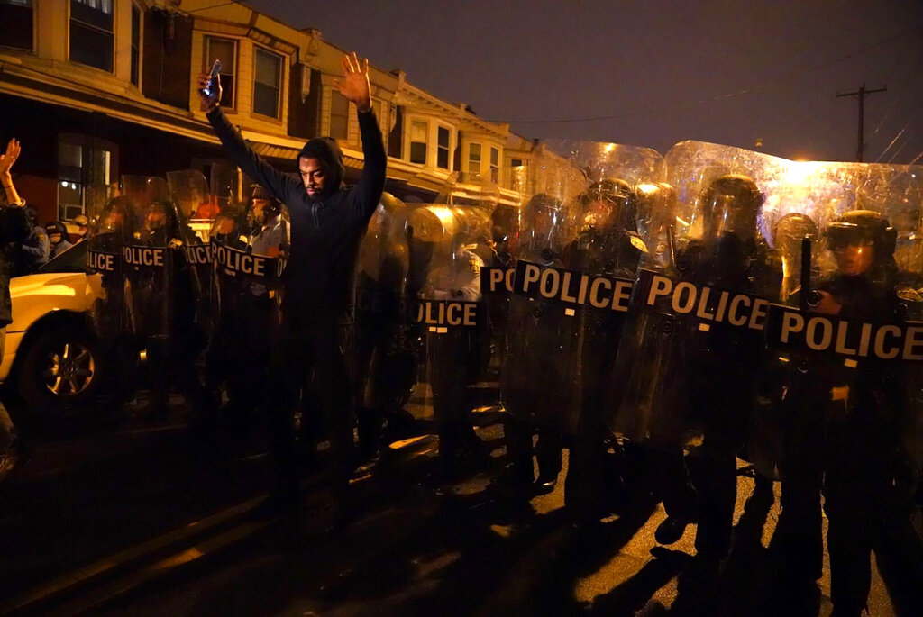 Sharif Proctor lifts his hands up in front of the police line during a protest in response to the police shooting of Walter Wallace Jr., Monday, Oct. 26, 2020, in Philadelphia. (Jessica Griffin/The Philadelphia Inquirer via AP)