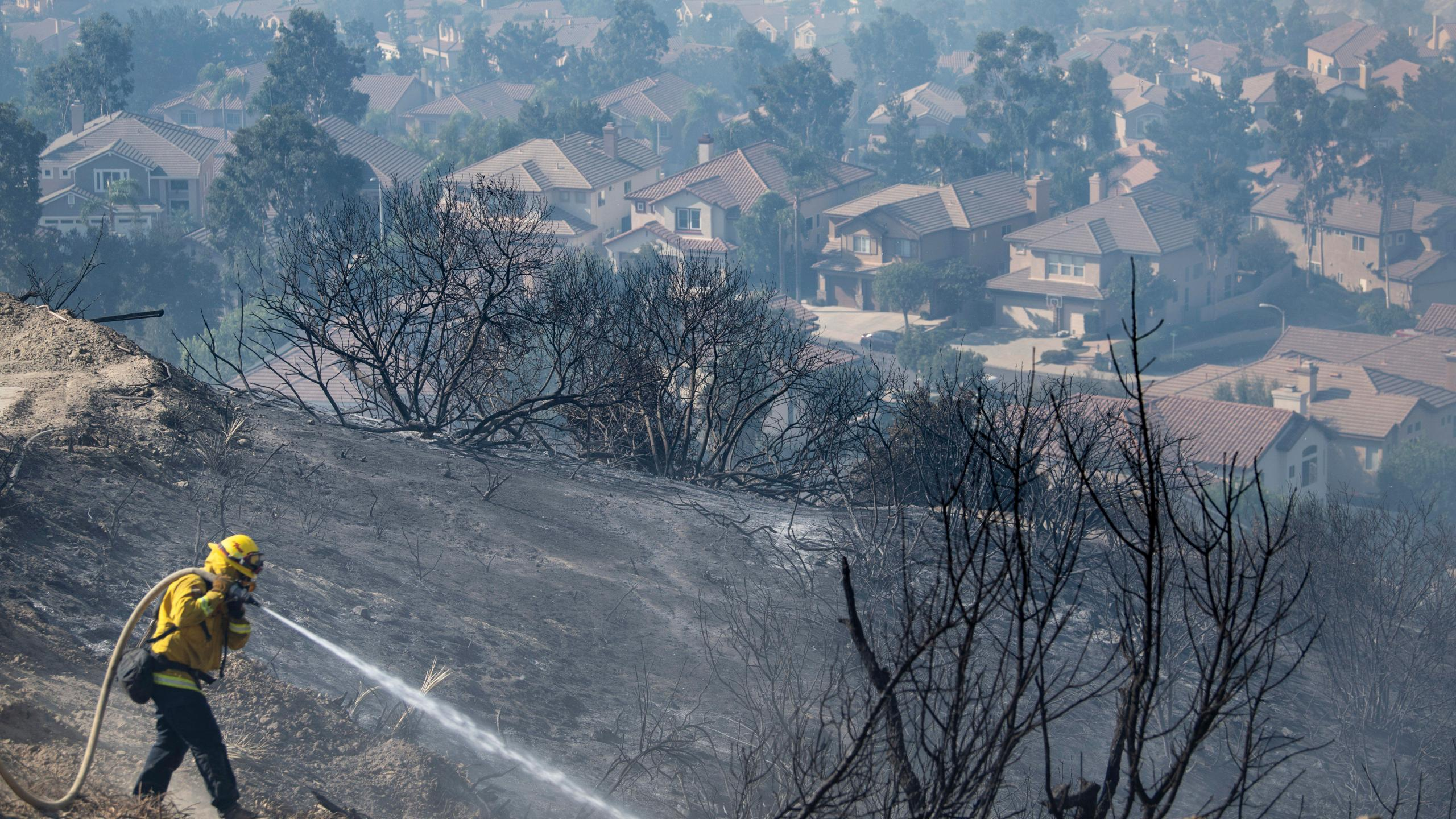 Firefighters work flames from the Silverado Fire atop a hill above homes in Foothill Ranch where a mandatory evacuation is in place on Tuesday, Oct. 27, 2020. (Mindy Schauer/The Orange County Register via AP)