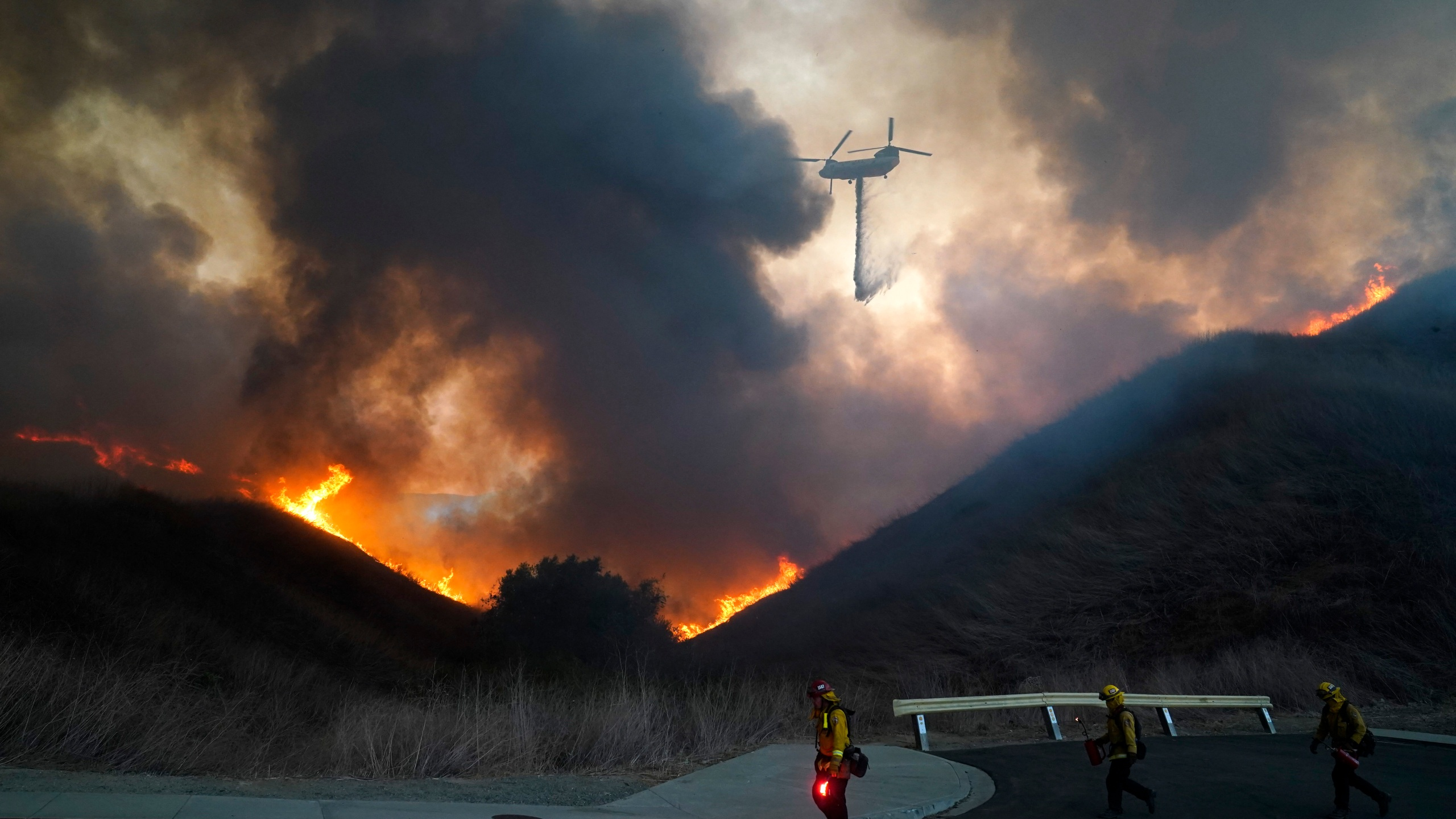 A helicopter drops water as firefighters walk with drip torches to set a backfire against the Blue Ridge Fire on Oct. 27, 2020, in Chino Hills. (Jae C. Hong / Associated Press)