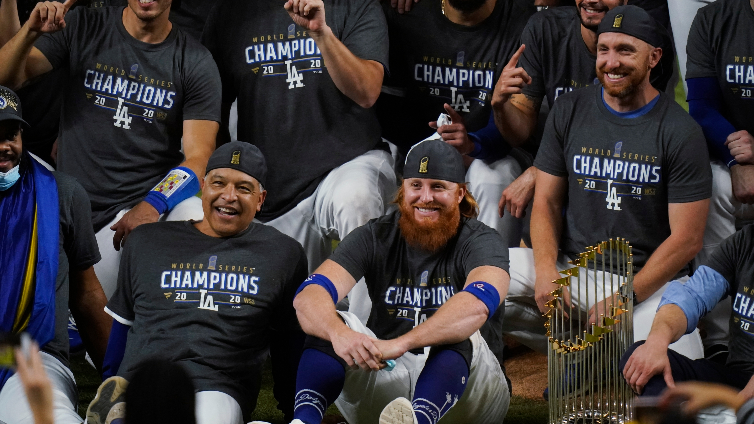 Los Angeles Dodgers manager Dave Roberts and third baseman Justin Turner pose for a group picture after the Dodgers defeated the Tampa Bay Rays 3-1 in Game 6 to win the baseball World Series, Tuesday, Oct. 27, 2020, in Arlington, Texas. The picture was taken after Turner was pulled from the game due to a positive coronavirus test. (AP Photo/Eric Gay)