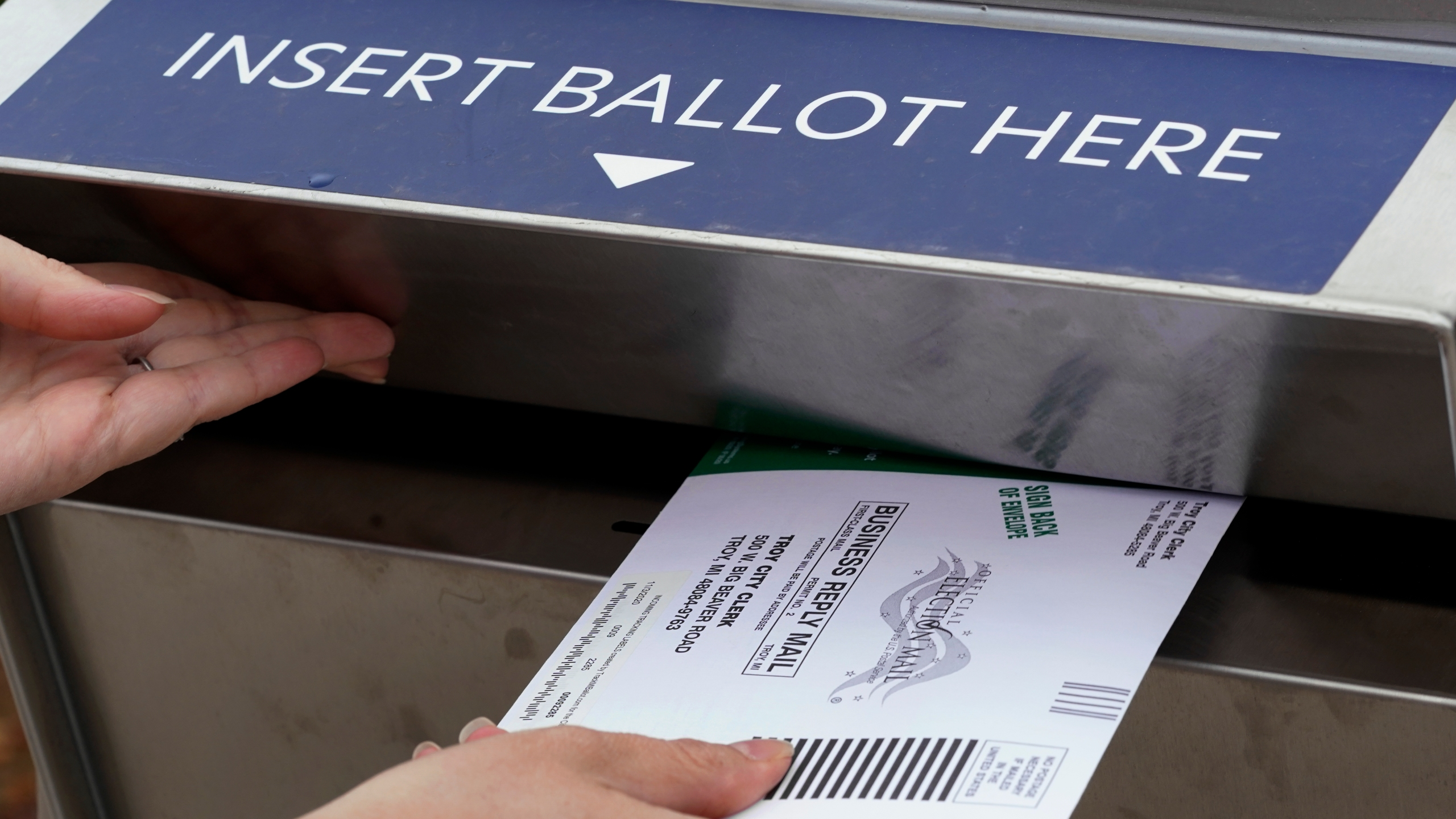 In this Thursday, Oct. 15, 2020, file photo, Nikki Schueller inserts her absentee voter ballot into a drop box in Troy, Mich. (Paul Sancya/AP)
