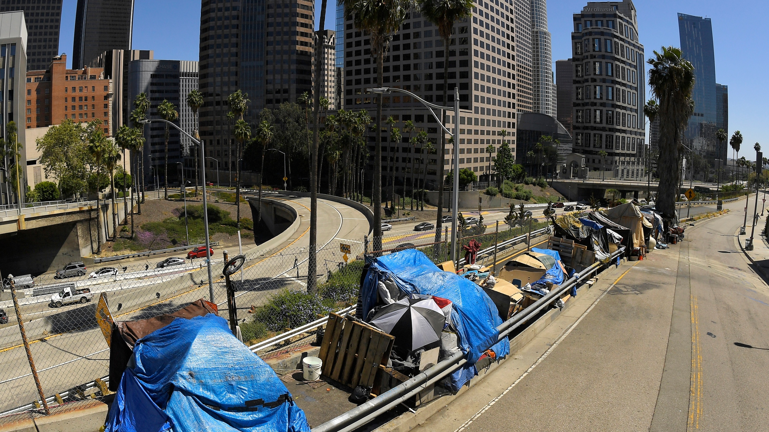 A homeless encampment is seen on Beaudry Avenue as traffic moves along Interstate 110 in downtown Los Angeles on May 21, 2020. (Mark J. Terrill / Associated Press)