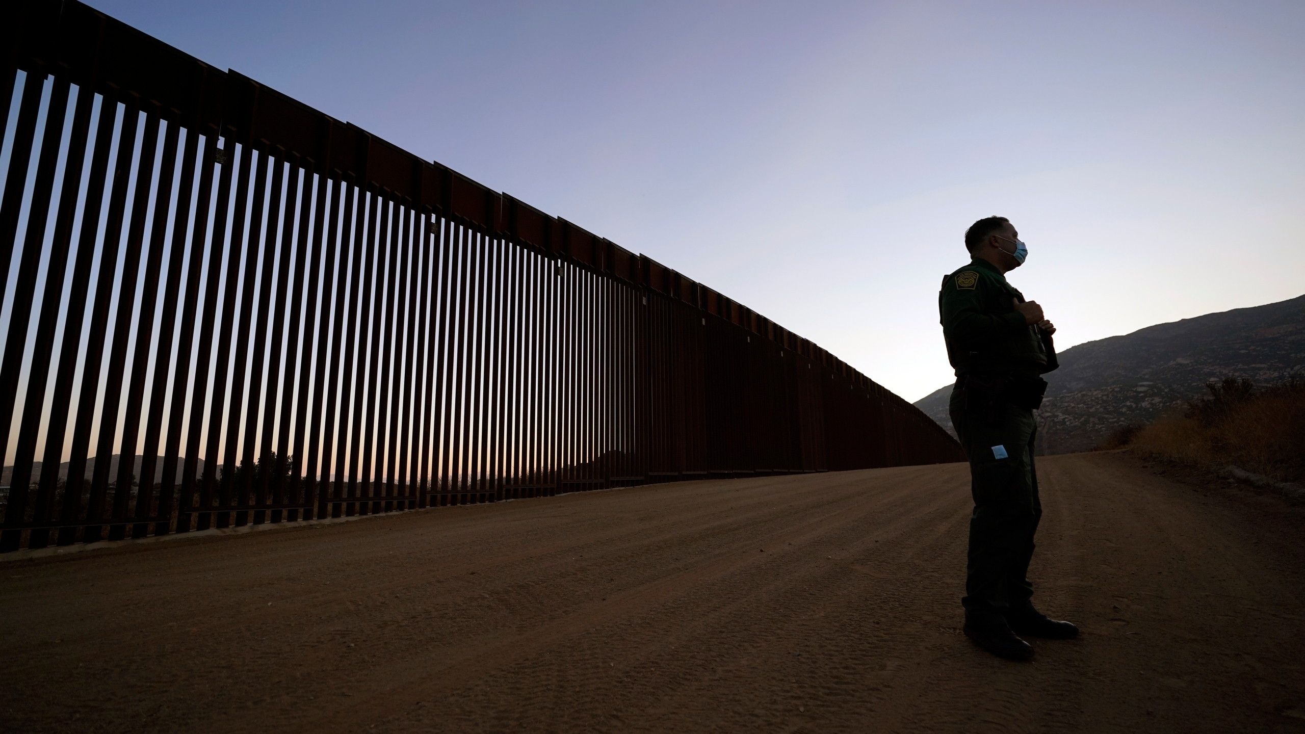 Border Patrol agent Justin Castrejon speaks in front of newly replaced border wall sections on Sept. 24, 2020, near Tecate, Calif. (AP Photo/Gregory Bull)