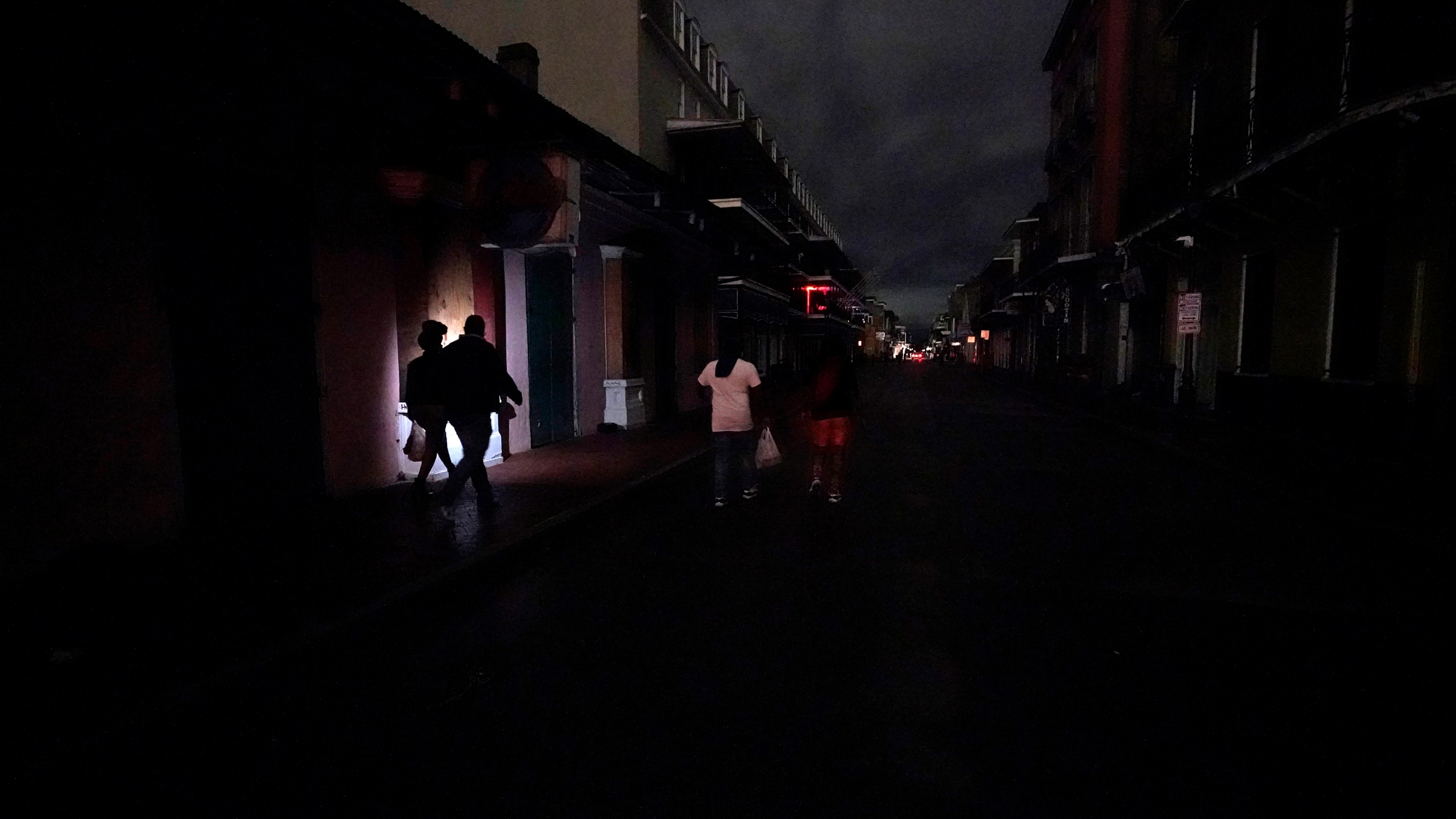 A darkened Bourbon Street is illuminated only by passers-by with lights and car headlights New Orleans' French Quarter on Oct. 28, 2020, after Hurricane Zeta passed through leaving much of the city and metro area without power. (Gerald Herbert / Associated Press)