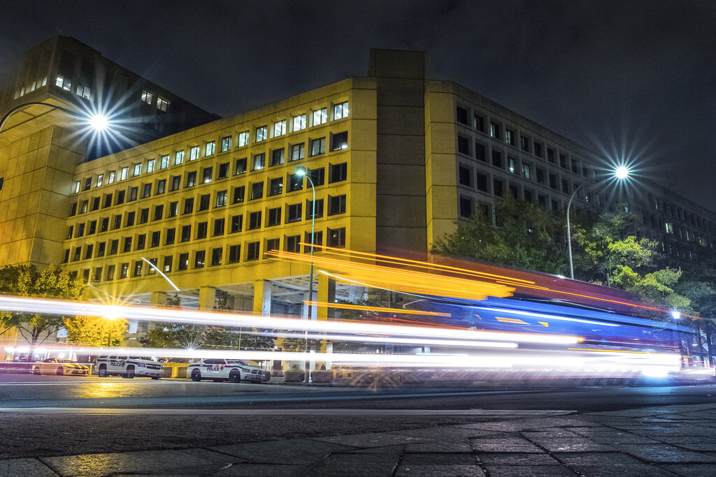 In this Nov. 1, 2017, file photo, traffic along Pennsylvania Avenue in Washington streaks past the Federal Bureau of Investigation headquarters building. In an alert on Oct. 28, 2020, the FBI and other federal agencies warned that cybercriminals are unleashing a wave of data-scrambling extortion attempts against the U.S. healthcare system.(AP Photo/J. David Ake, File)