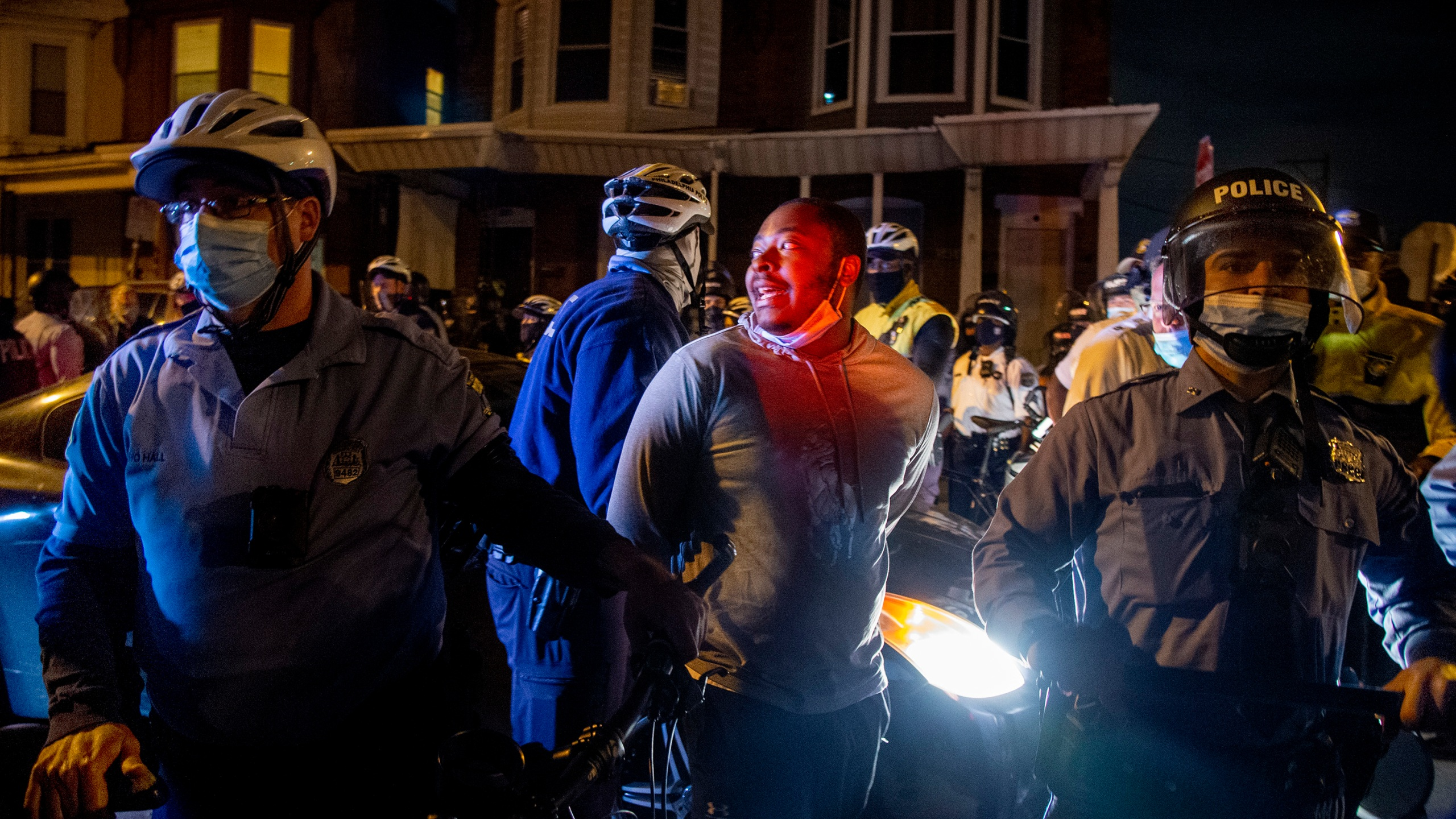 A person is handcuffed and detained by police in Philadelphia on Oct. 28, 2020, two days after Walter Wallace Jr. was killed by police officers. (Tom Gralish/The Philadelphia Inquirer via Associated Press)
