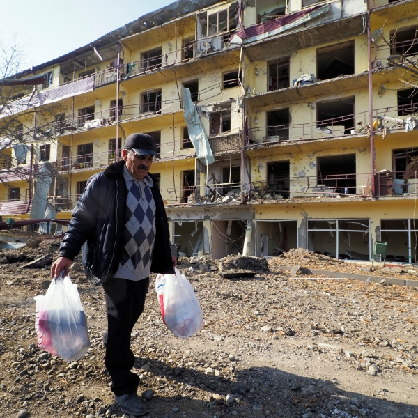 Vovik Zakharian, 72, walks past his apartment building damaged by shelling by Azerbaijan's forces during a military conflict in Shushi, in the separatist region of Nagorno-Karabakh, on Oct. 29, 2020. (Associated Press)