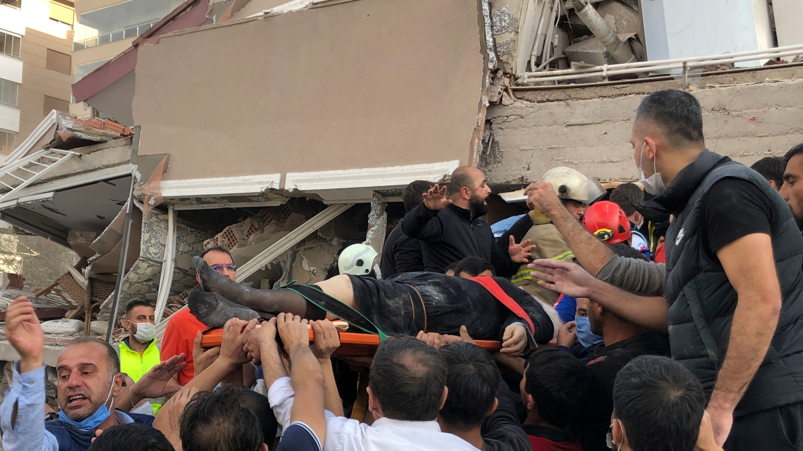 Rescue workers and local people carry a wounded person found in the debris of a collapsed building, in Izmir, Turkey, on Oct. 30, 2020, after a strong earthquake in the Aegean Sea has shaken Turkey and Greece. (Ismail Gokmen / Associated Press)