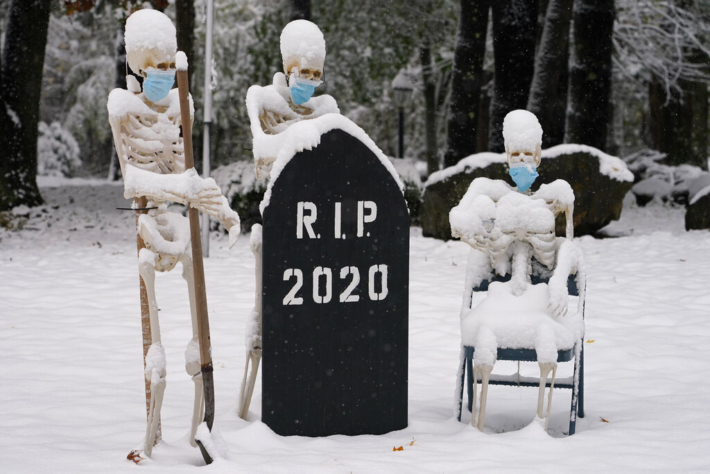 Snow falls on masked skeletons ready to bury the year 2020 on Oct. 30, 2020, on a lawn in North Andover, Mass. (AP Photo/Elise Amendola)