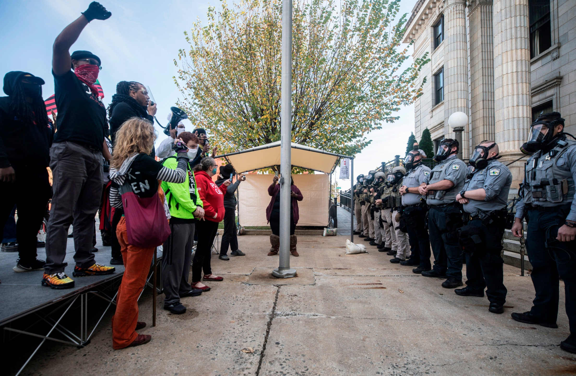 Protesters and Alamance County sheriff's deputies in riot gear face off in front of the courthouse in Graham, N.C. on Saturday, Oct. 31, 2020 before pepper spray was used and several people were arrested. (Julia Wall/The News & Observer via AP)