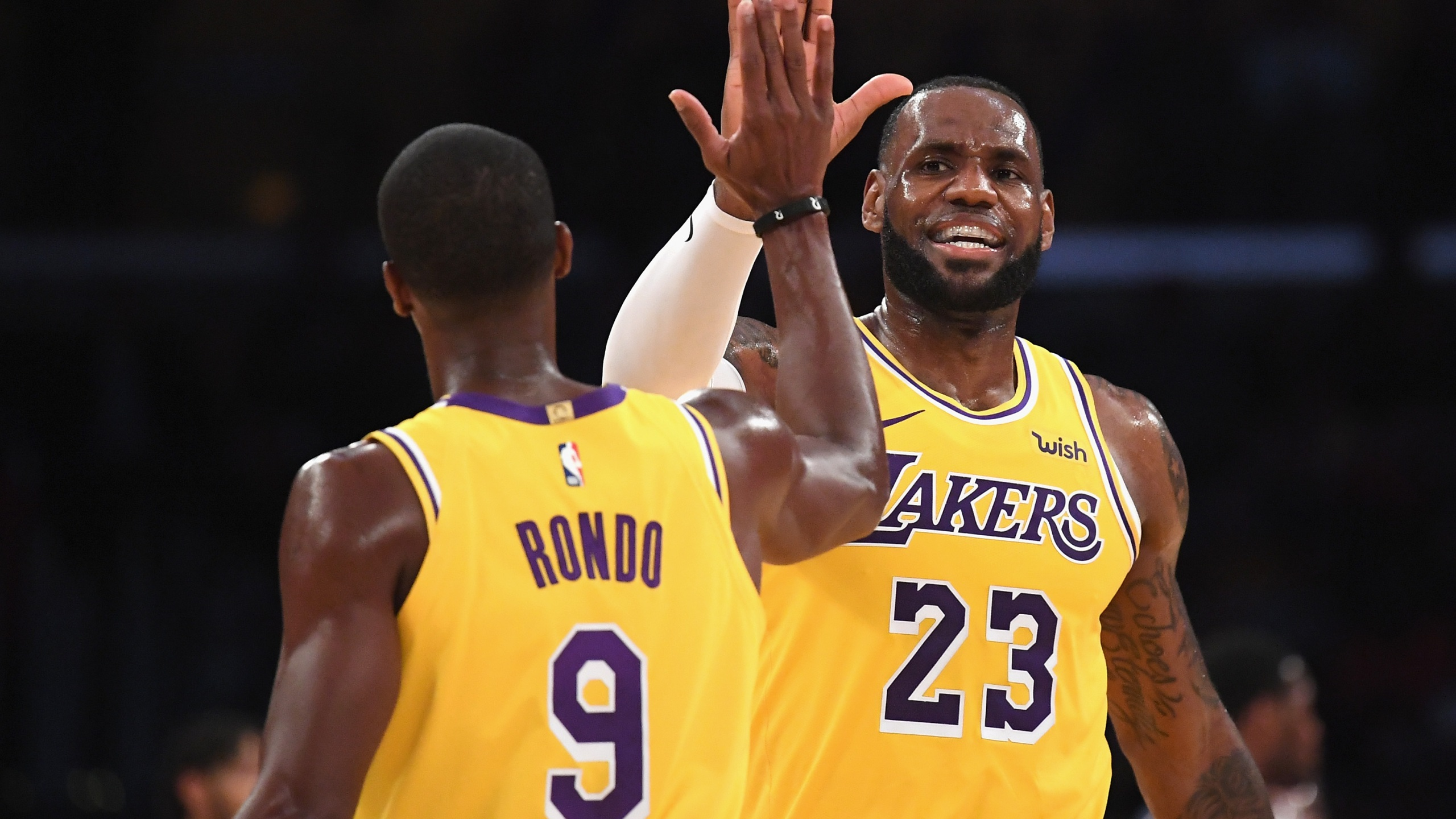 LeBron James of the Los Angeles Lakers high fives Rajon Rondo during a preseason game against the Denver Nuggets at Staples Center on Oct. 2, 2018. (Harry How / Getty Images)