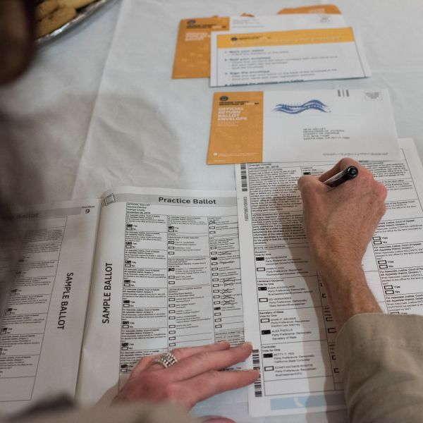 A voter completes her mail-in ballot at a ballot party at a private residence in Laguna Niguel on Oct. 24, 2018. (ROBYN BECK/AFP via Getty Images)