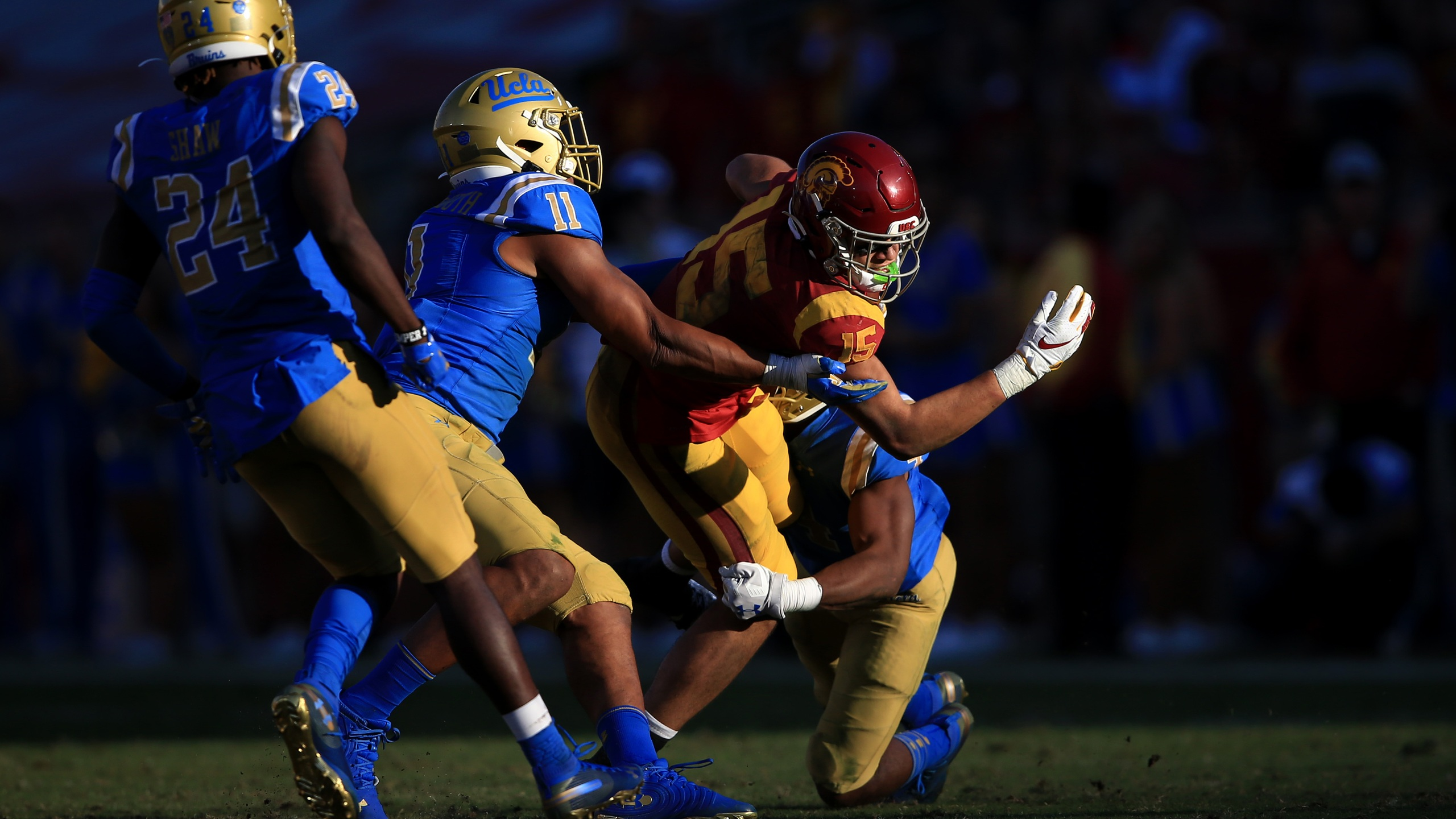 Stephan Blaylock #4, Drake London #15 of the USC Trojans is tackled by Keisean Lucier-South #11 and Jay Shaw #24 of the UCLA Bruins during the second half of a game at Memorial Coliseum on Nov. 23, 2019 in Los Angeles. (Sean M. Haffey/Getty Images)