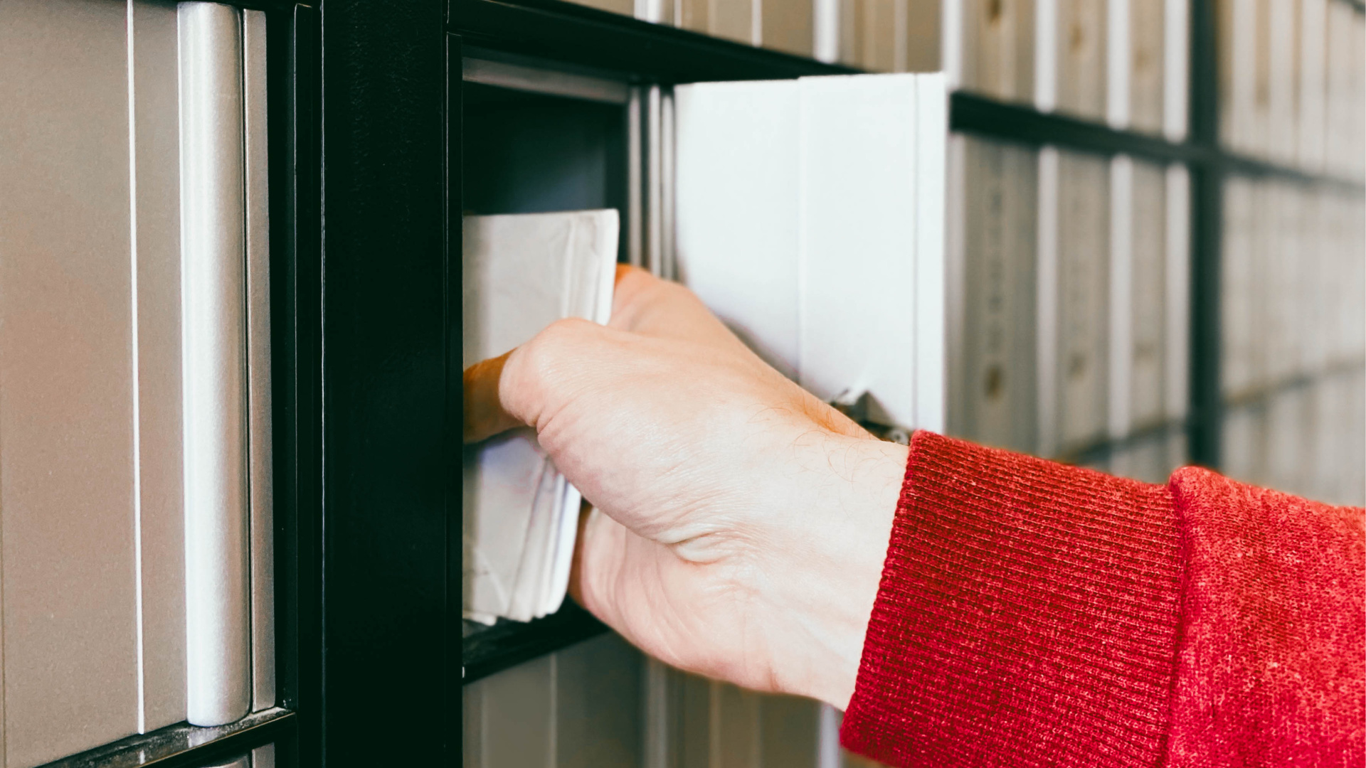 A woman pulls out a stack of letters from a mail box in this undated file photo. (Getty Images)