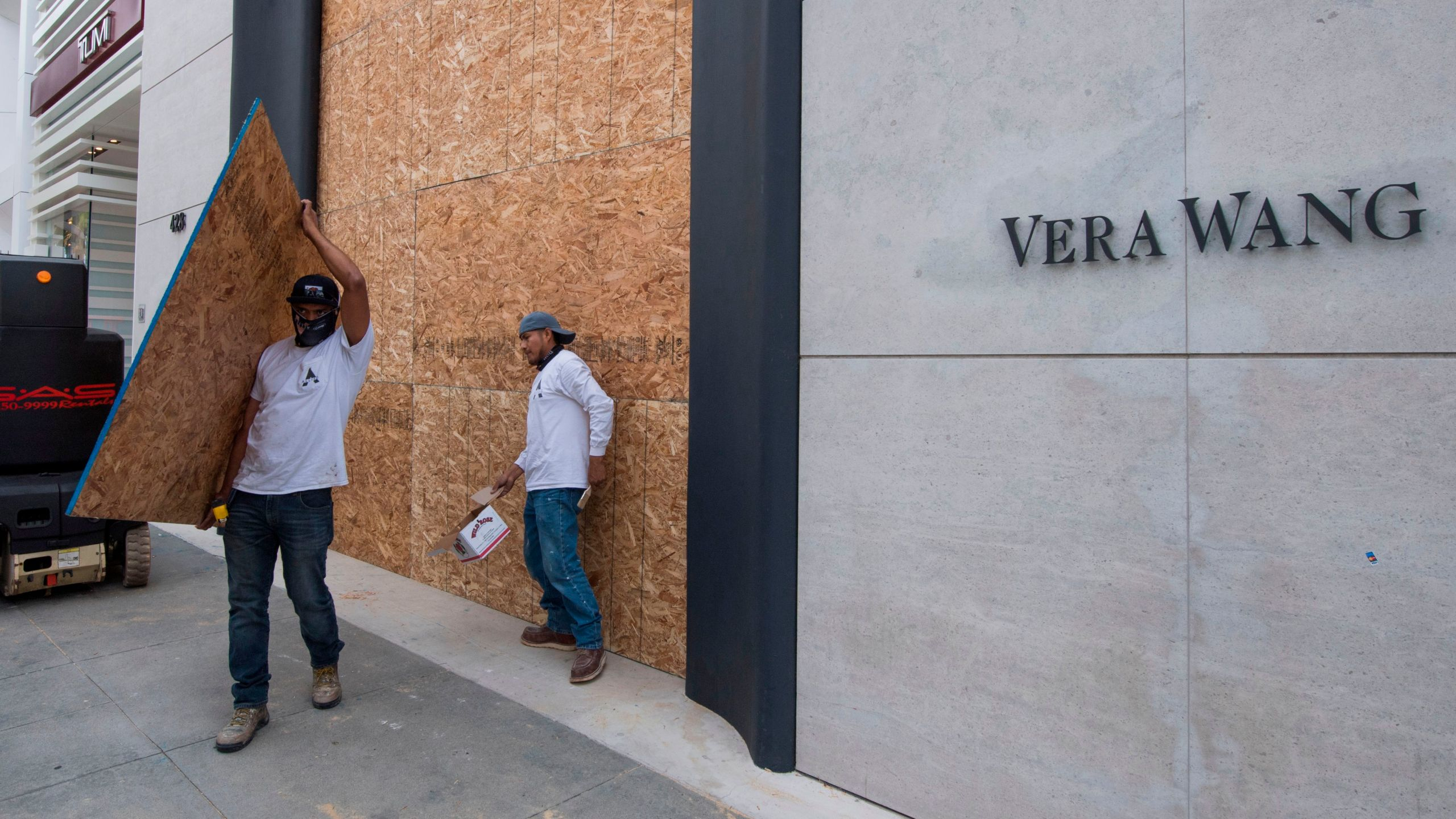 Workers put up protective boarding at a looted Vera Wang store on the iconic Rodeo Drive, after demonstrators protested the death of George Floyd in Beverly Hills, California on May 31, 2020. (Photo by Mark RALSTON / AFP) (Photo by MARK RALSTON/AFP via Getty Images)
