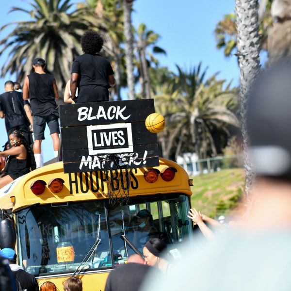 """Protesters shoot a basketball at the """"hoop bus"""" after riding their bikes to the beach during the Bike Rides for Black Lives demonstration in support of the Black Lives Matter in Santa Monica, California, on July 12, 2020. (CHRIS DELMAS/AFP via Getty Images)"""