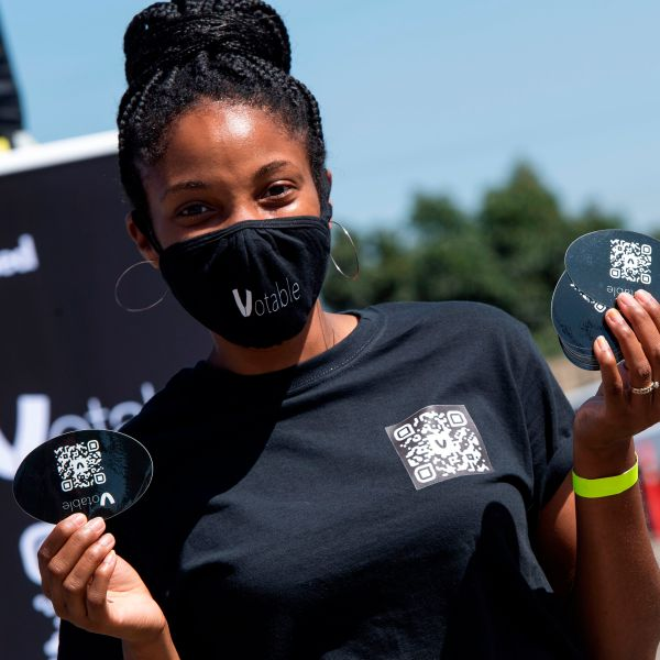 A volunteer shows the bar code that she gives to people to register to vote online at the Gen-Z Drive Up Voter Registration Event organized by BeWoke Vote, Sept. 19, 2020, in Compton, California. (VALERIE MACON / AFP via Getty Images)