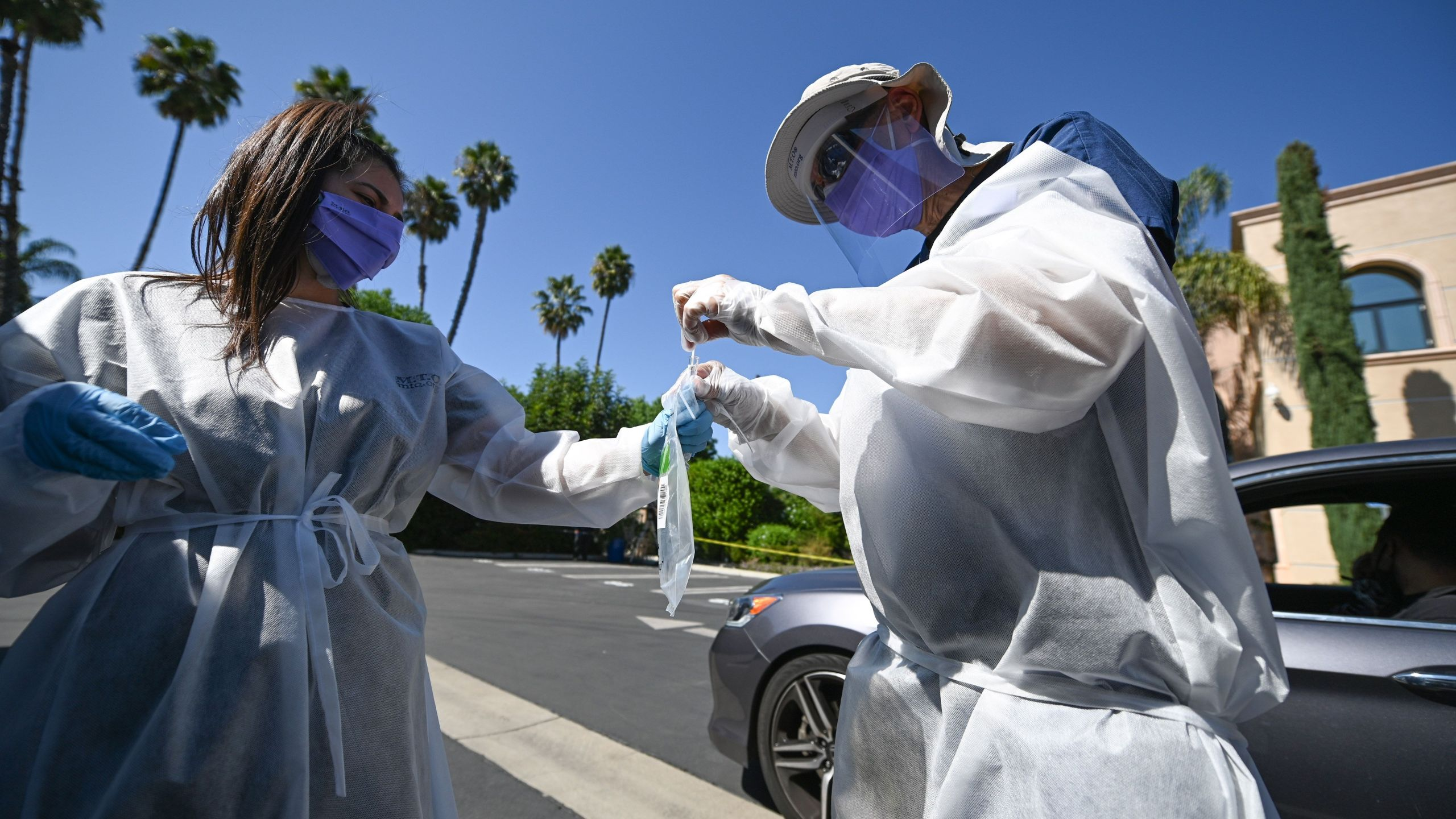 Healthcare workers collect a test sample at a drive-through coronavirus testing center at M.T.O. Shahmaghsoudi School of Islamic Sufism on Sept. 29, 2020 in Los Angeles. (Robyn Beck / AFP via Getty Images)