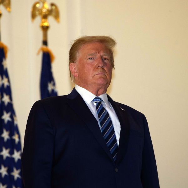 President Donald Trump looks out from the Truman Balcony upon his return to the White House from Walter Reed Medical Center, where he underwent treatment for COVID-19, in Washington, D.C., on Oct. 5, 2020. (NICHOLAS KAMM / AFP via Getty Images)