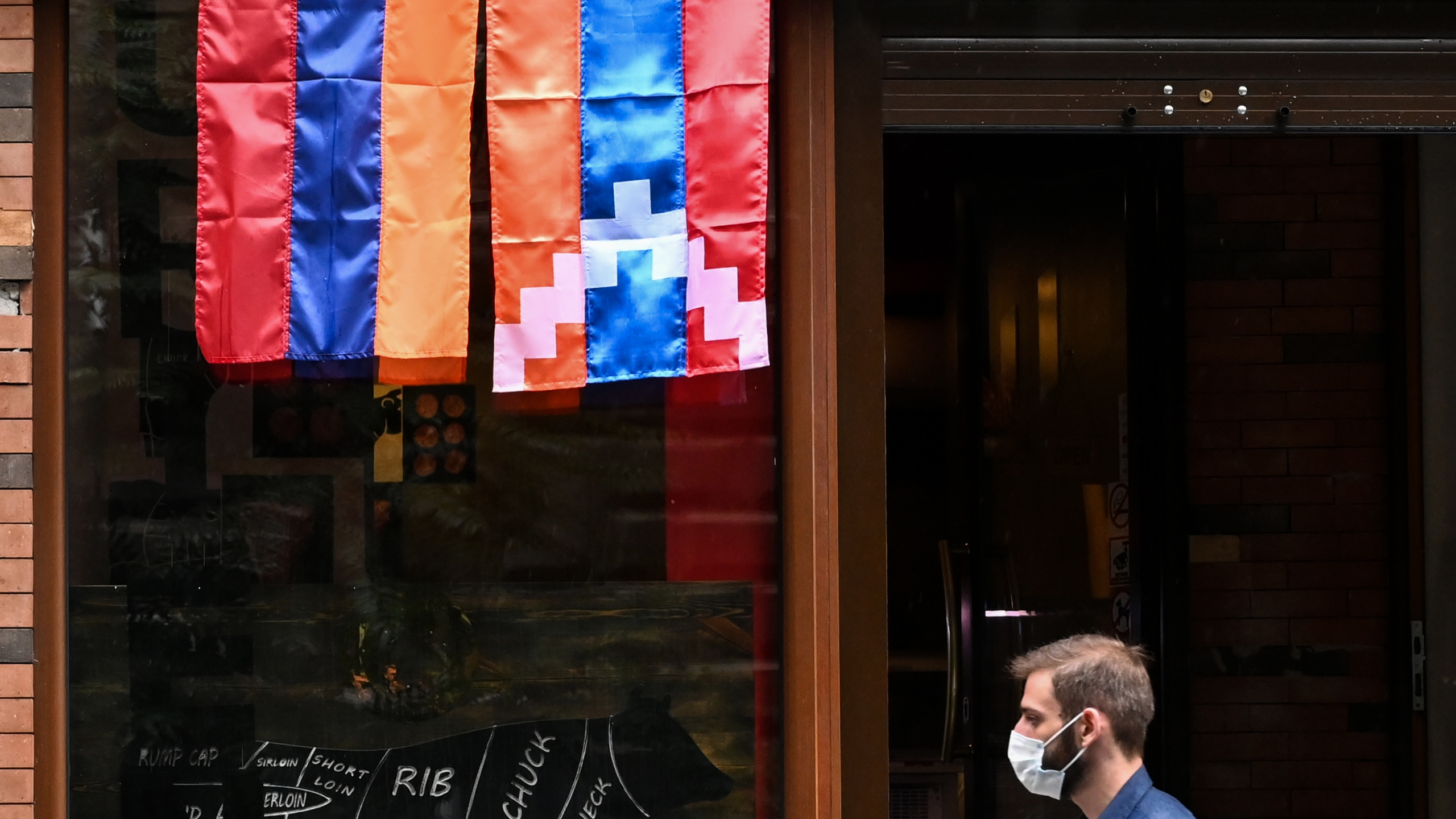 A man walks past a shop decorated with flags of Armenia and the breakaway Nagorno-Karabakh region in Yerevan, Armenia's capital, on Oct. 6, 2020. (AFP via Getty Images)
