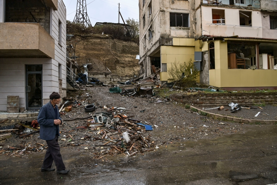 An elderly man walks past destroyed buildings in the breakaway Nagorno-Karabakh region's main city of Stepanakert on Oct. 6, 2020, during the ongoing fighting between Armenia and Azerbaijan over the disputed region. (ARIS MESSINIS/AFP via Getty Images)