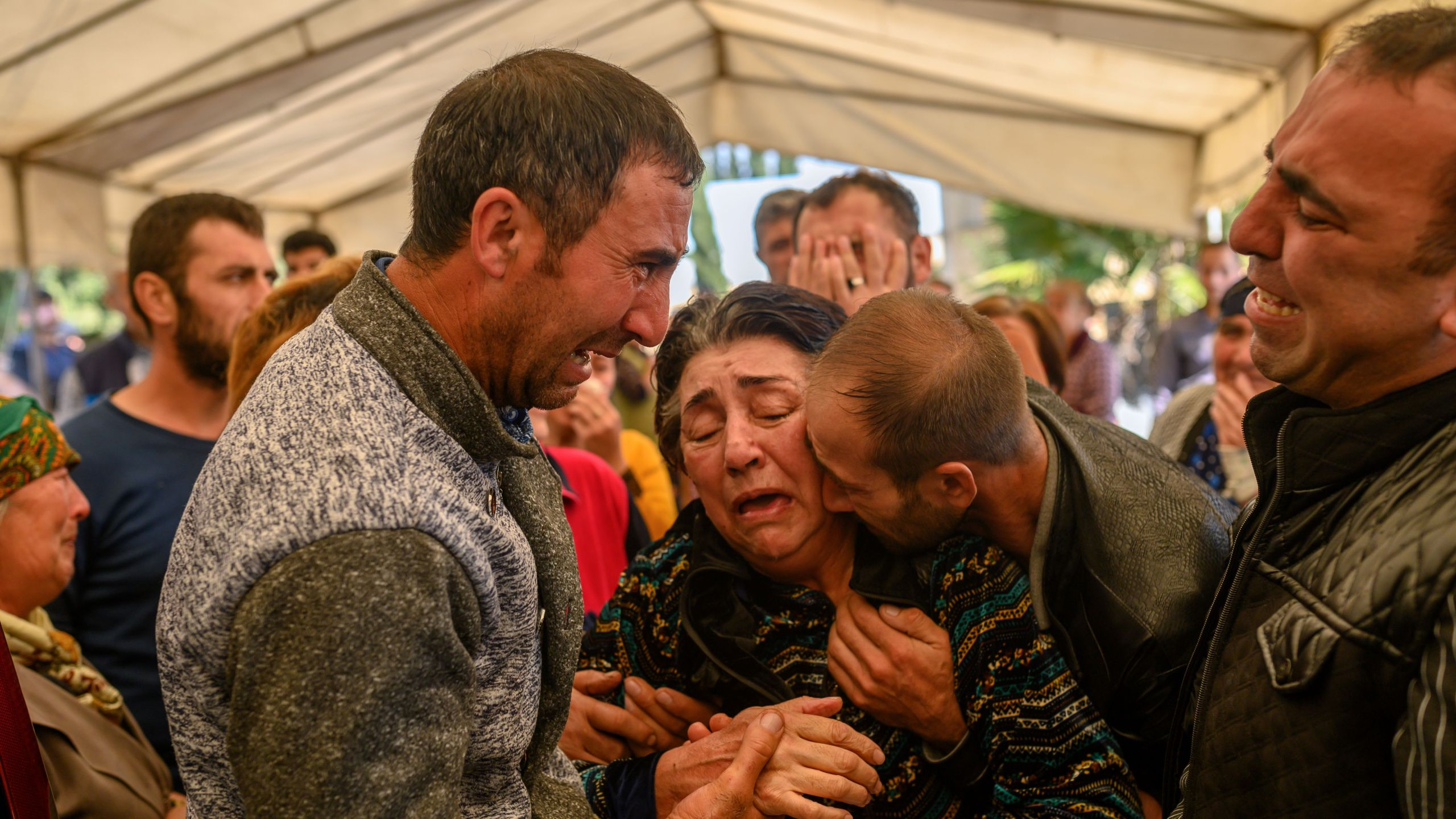 Relatives of Royal Sahnazarov, his wife Zuleyha Sahnazarova and their daughter Medine Sahnazorava, who were killed when a rocket hit their home, mourn during their funeral in the city of Ganja, Azerbaijan, on Oct. 17, 2020 during fighting over the breakaway region of Nagorno-Karabakh. (BULENT KILIC/AFP via Getty Images)