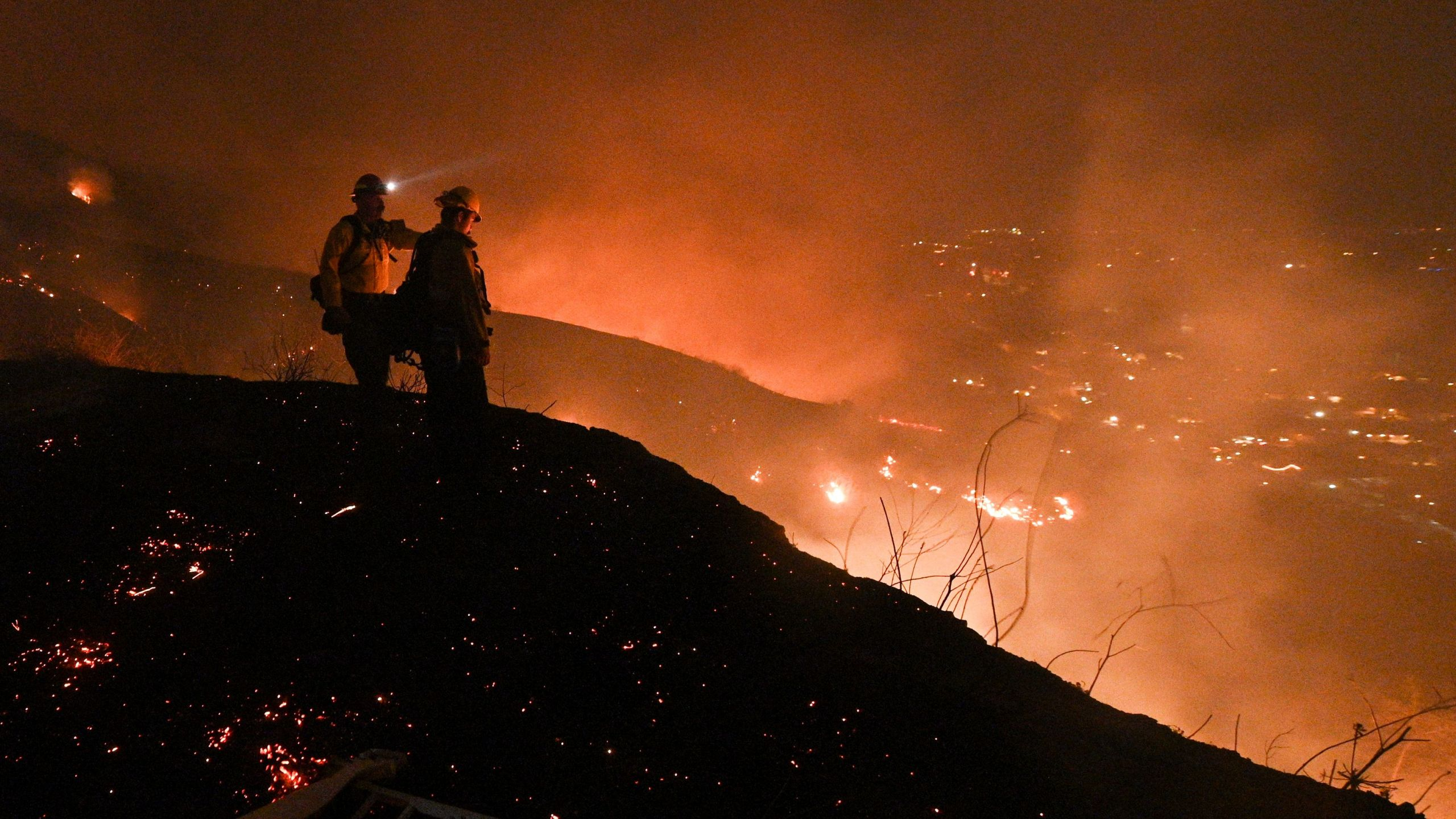 Firefighters look out over a burning hillside as they fight the Blue Ridge Fire in Yorba Linda on Oct. 26, 2020. (Robyn Beck / AFP / Getty Images)