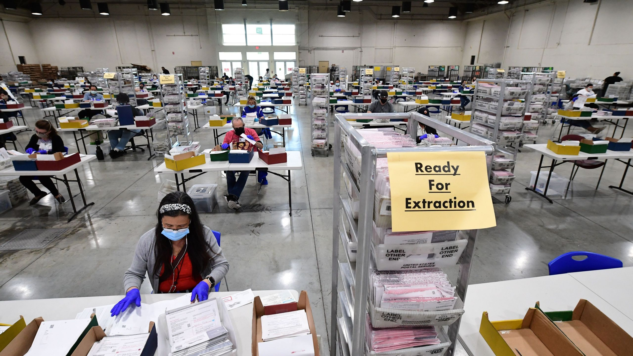 Election workers extract mail-in ballots from their envelopes and examine the ballot for irregularities at the Los Angeles County Registrar Recorders' mail-in ballot processing center at the Pomona Fairplex in Pomona on Oct. 28, 2020. (ROBYN BECK/AFP via Getty Images)