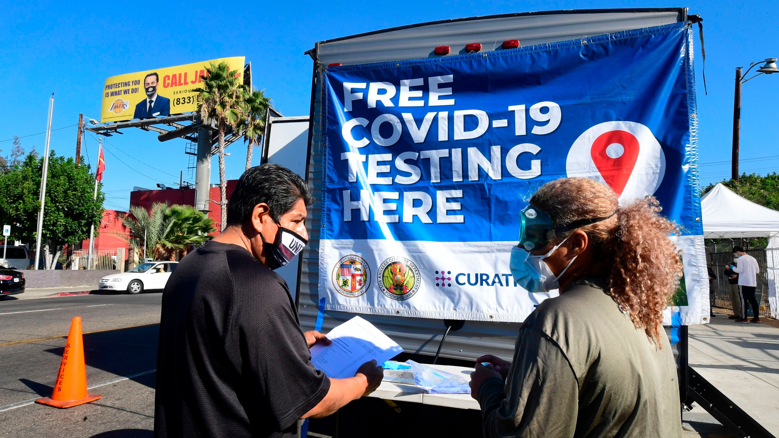 A man asks a volunteer questions at a pop-up COVID-19 test site in Los Angeles on Oct. 29, 2020. (FREDERIC J. BROWN/AFP via Getty Images)