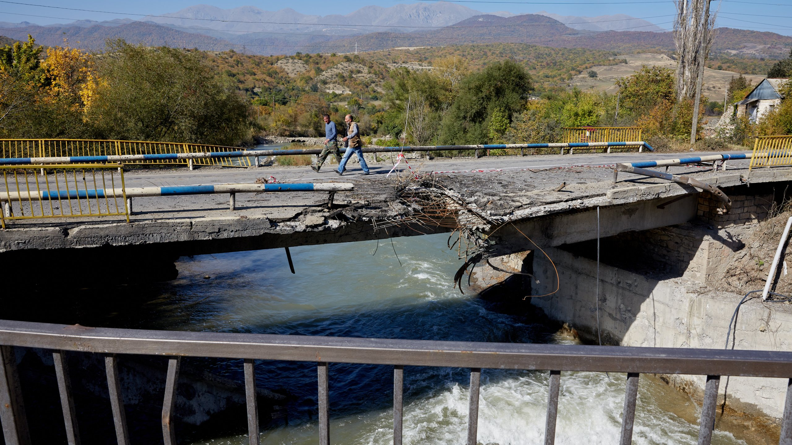 Two men walk across a bridge in Getavan, Nagorno-Karabakh, that was hit by an Azeri missile, on Oct. 14, 2020. (Alex McBride/Getty Images)