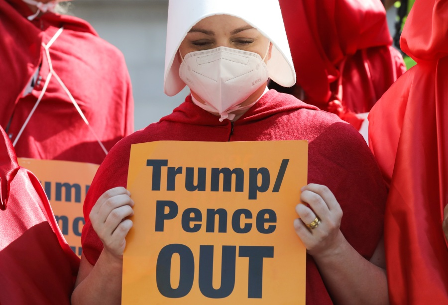 """A woman in a """"Handmaid's Tale"""" costume demonstrate during a Women's March on Oct. 17, 2020 in Los Angeles. (Mario Tama/Getty Images)"""
