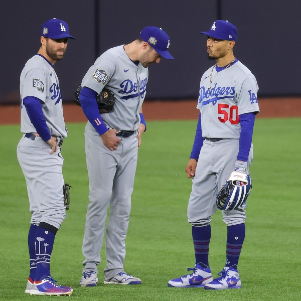 Chris Taylor, A.J. Pollock and Mookie Betts of the Los Angeles Dodgers talk during a pitching change against the Tampa Bay Rays during the seventh inning in Game Four of the 2020 MLB World Series at Globe Life Field on Oct. 24, 2020 in Arlington, Texas. (Ronald Martinez/Getty Images)