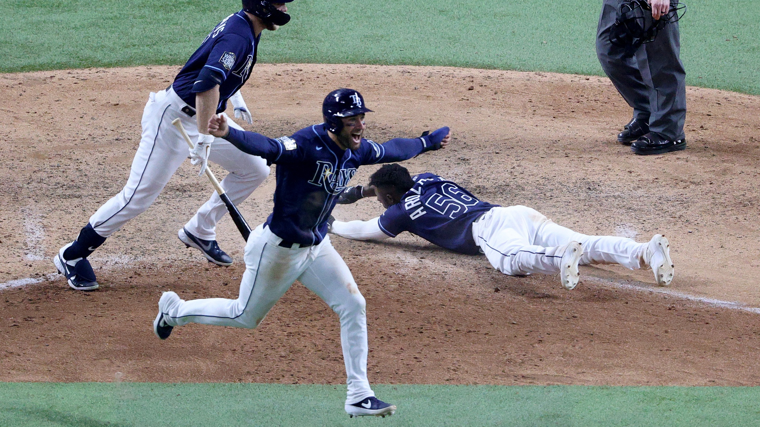 Randy Arozarena #56 of the Tampa Bay Rays slides into home plate during the ninth inning to score the game winning run to give his team the 8-7 victory as Kevin Kiermaier celebrates against the Los Angeles Dodgers in Game Four of the 2020 MLB World Series at Globe Life Field on Oct. 24, 2020, in Arlington, Texas. (Sean M. Haffey/Getty Images)