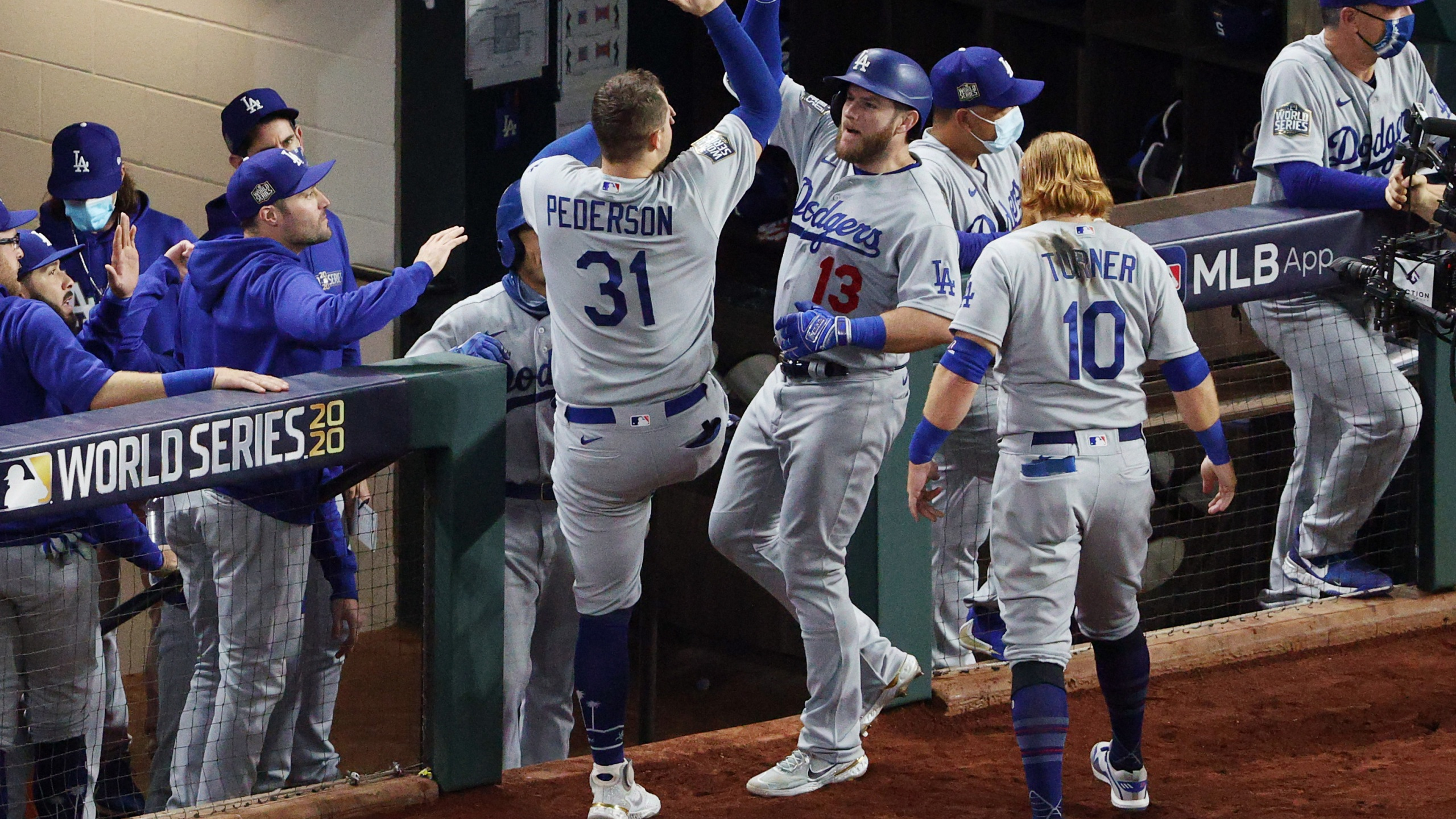 Max Muncy #13 of the Los Angeles Dodgers is congratulated by Joc Pederson #31 and Justin Turner #10 after hitting a solo home run against the Tampa Bay Rays during the fifth inning in Game Five of the 2020 MLB World Series at Globe Life Field on Oct. 25, 2020, in Arlington, Texas. (Sean M. Haffey/Getty Images)