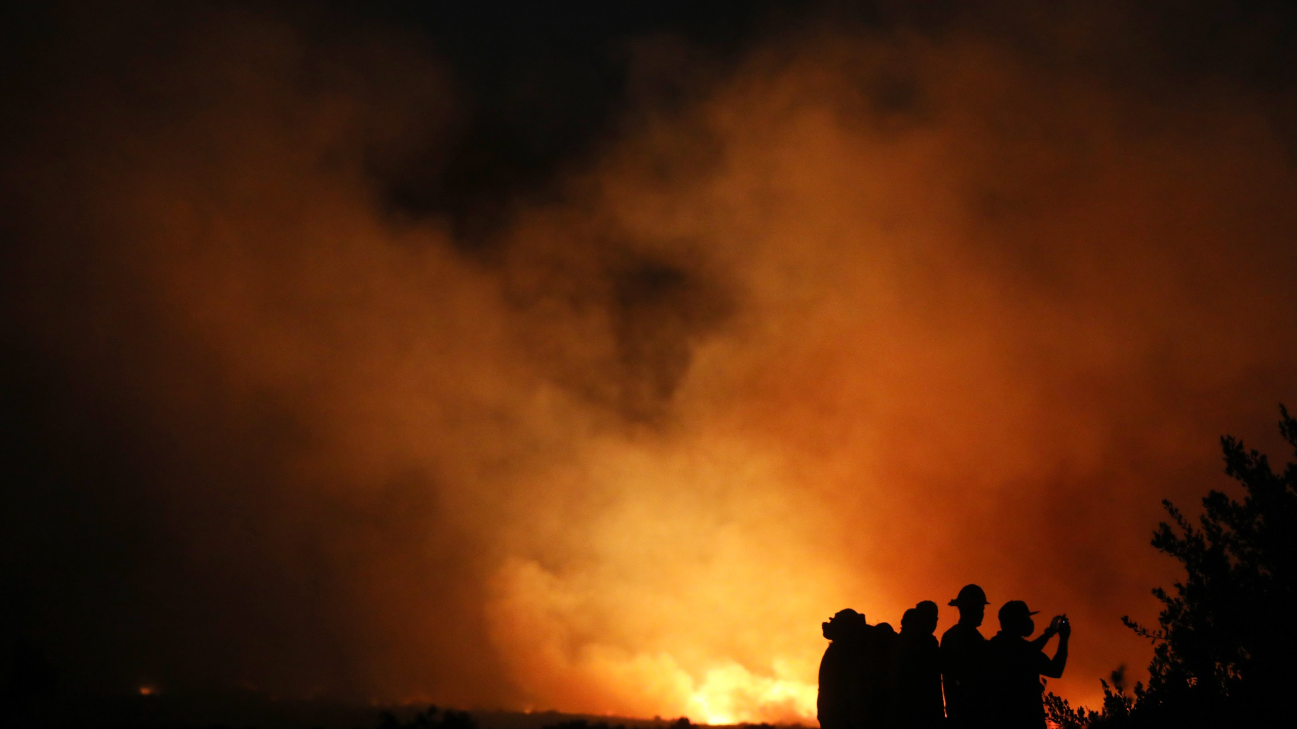 Firefighters and onlookers gather during the Silverado Fire in Orange County on Oct. 26, 2020, in Lake Forest. (Mario Tama/Getty Images)