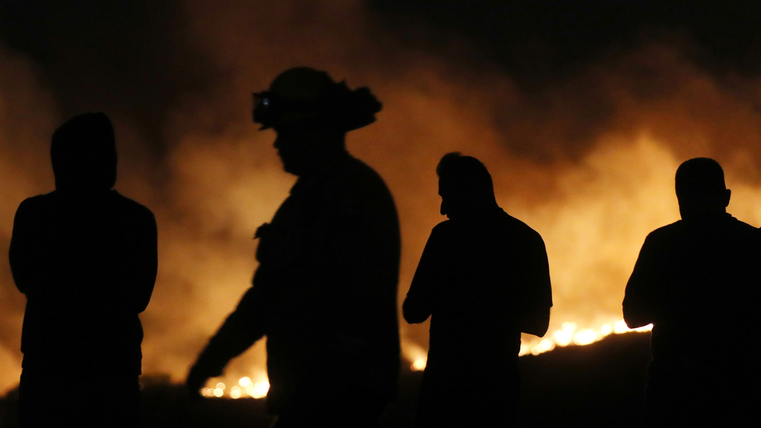A firefighter walks past onlookers gathered during the Silverado Fire in Orange County on October 26, 2020 in Lake Forest, California. (Photo by Mario Tama/Getty Images)