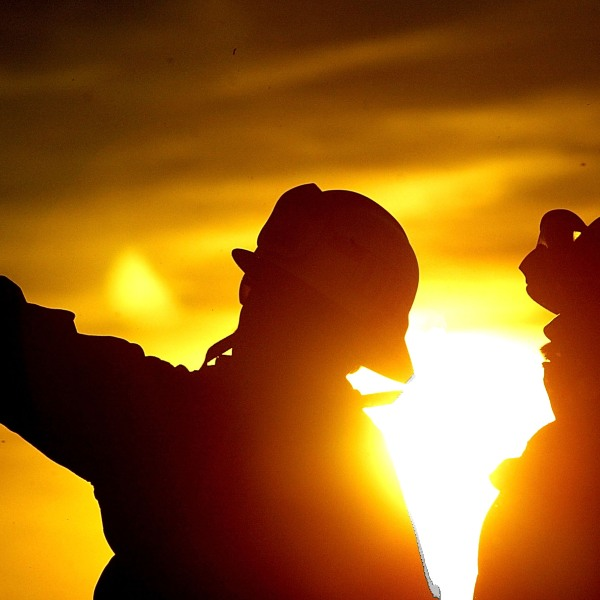 Firefighters talk while they battle the Crestline Wildfire in Los Angeles County Oct. 28, 2003. (Carlo Allegri/Getty Images)