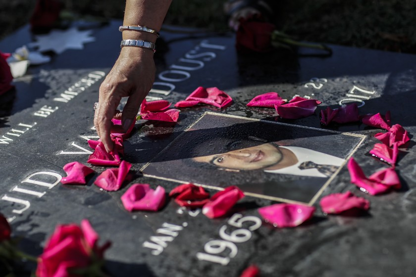 Majid Vatandoust died of colon cancer at age 52, three years after a request for a colonoscopy was denied by a specialist working for L.A. County despite tests that showed clear indicators of the disease. A woman arranges flowers at his gravestone in this undated photo. (Robert Gauthier / Los Angeles Times)