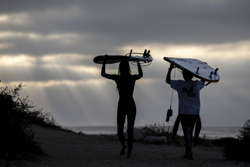 Young surfers carry their boards on their heads as they leave Rat Beach in Palos Verdes Estates in October 2020. (Jay L. Clendenin / Los Angeles Times)