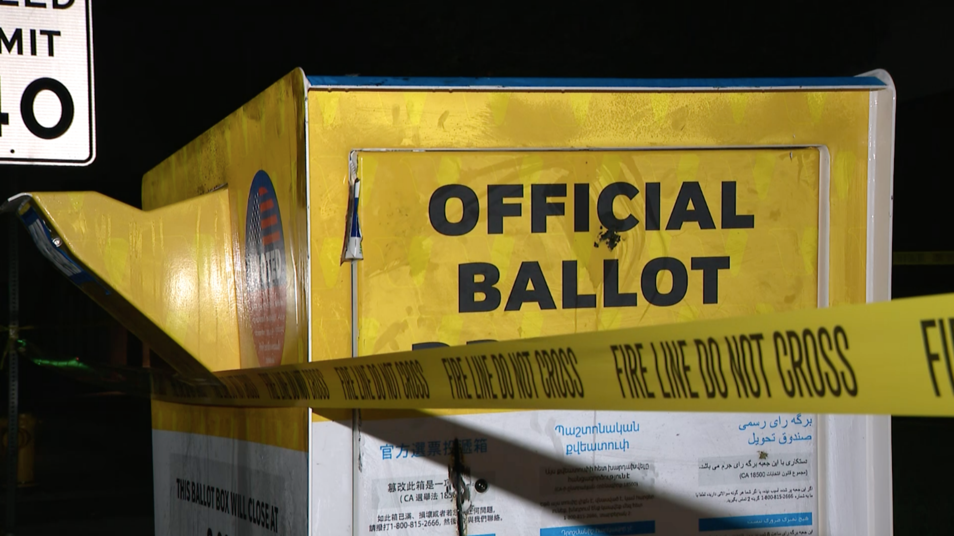 "A tape that reads ""fire line do not cross"" is seen around an official ballot drop box outside the Baldwin Park Library on Oct. 19, 2020. (KTLA)"