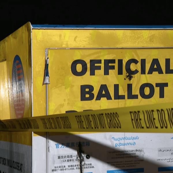 "A tape that reads ""fire line do not cross"" is seen around an official ballot drop box outside the Baldwin Park Library on Oct. 19, 2020. (KTLA)"