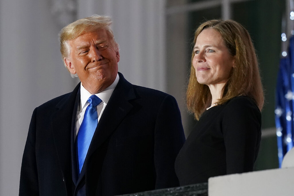 President Donald Trump and Amy Coney Barrett stand on the Blue Room Balcony after Supreme Court Justice Clarence Thomas administered the Constitutional Oath to her on the South Lawn of the White House White House in Washington on Monday. Barrett was confirmed to be a Supreme Court justice by the Senate earlier in the evening. (AP Photo/Patrick Semansky)