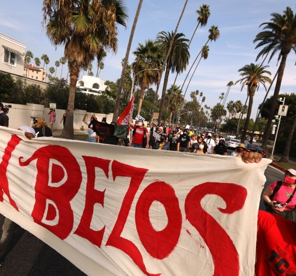 "Workers and advocates in Beverly Hills protest Amazon's working conditions on Oct. 4, 2020. Amazon worker Derrick Palmer, right, helps carry a ""Tax Bezos"" banner during a march to Bezos' mansion to lobby for higher wages, the right to unionize and a series of reforms in the way the company handles the COVID-19 crisis. (Genaro Molina / Los Angeles Times)"