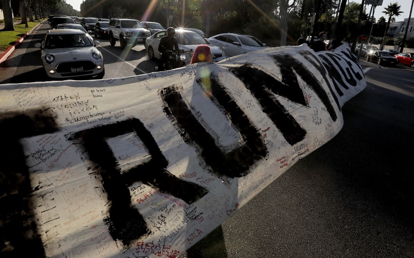 "A Sept. 17, 2019 file photo shows a sign that reads ""Trump Pence."" A group of Trump supporters lined Santa Monica Boulevard in Beverly Hills on Oct. 3, 2020. (Luis Sinco / Los Angeles Times)"