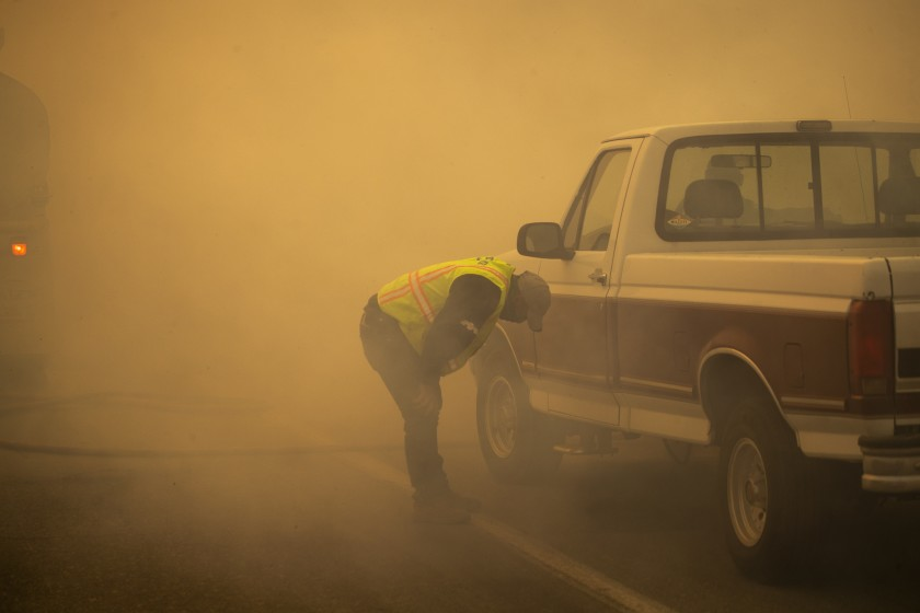 "A water truck operator is overcome with smoke after running through the advancing Silverado fire in Orange County on Monday. Two fires in Orange County are contributing to ""unhealthy"" air in Southern California, the worst in the nation.(Allen J. Schaben / Los Angeles Times)"