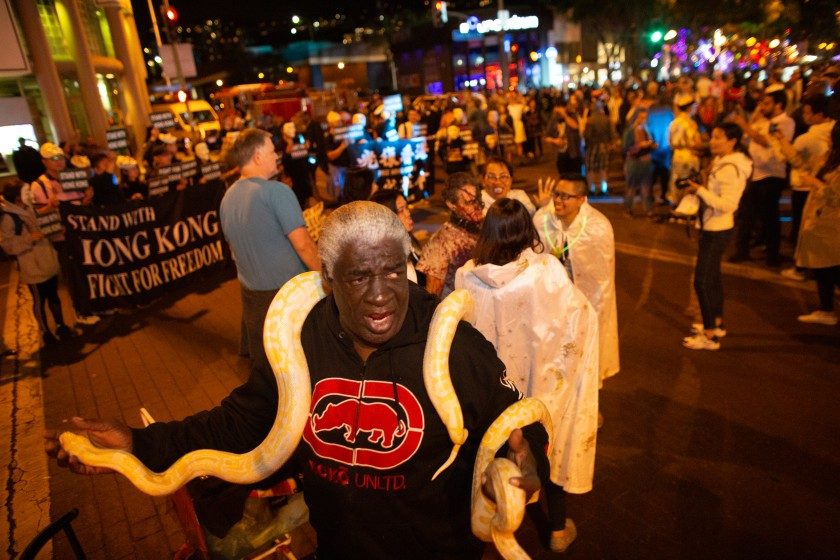 Ronald Johnson shows off his snake at the 2019 annual West Hollywood Carnaval along Santa Monica Boulevard. This year's event has been canceled because of the pandemic.(Jason Armond / Los Angeles Times)