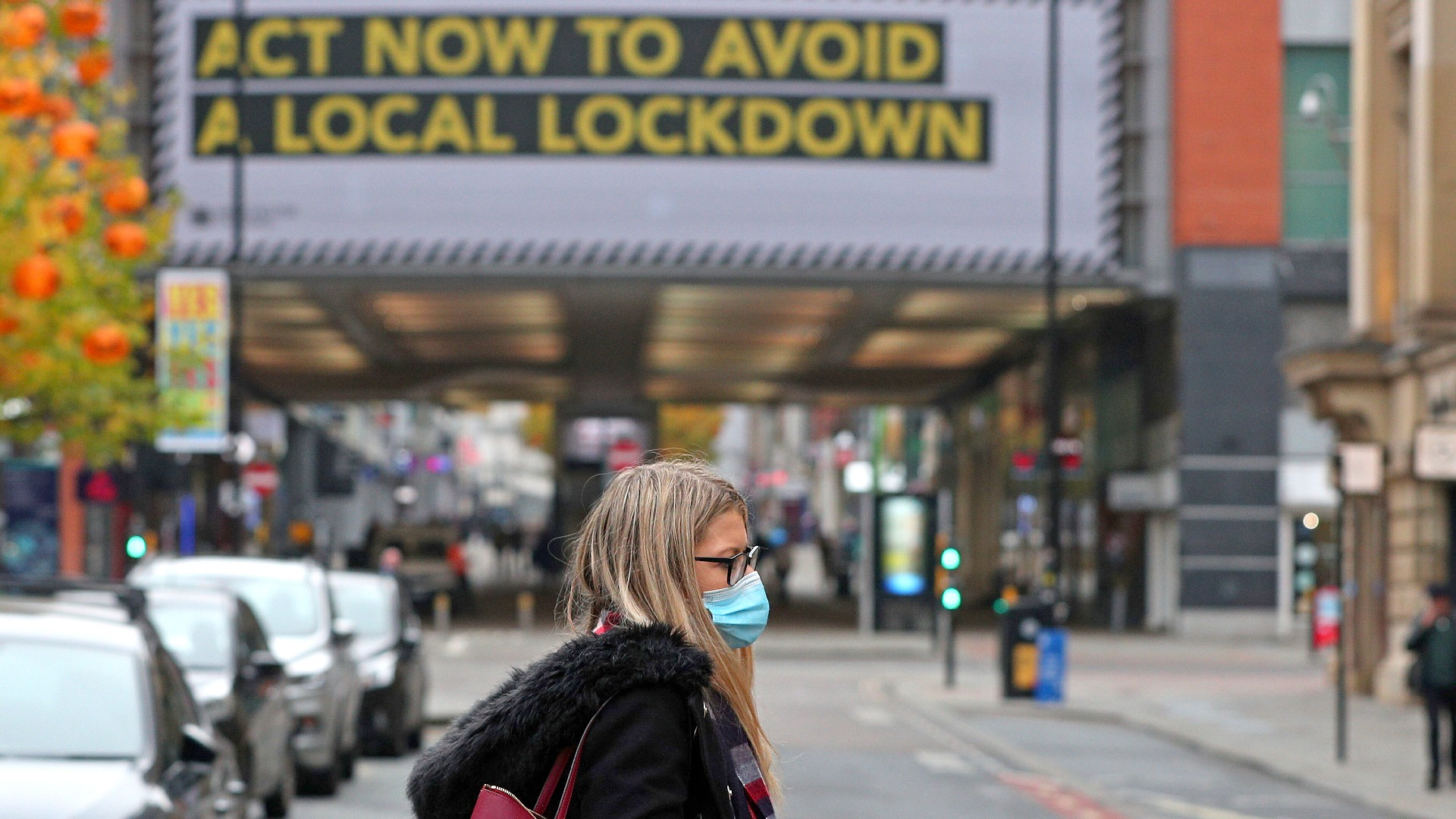 A woman wearing a face mask walks in Manchester, England, Monday, Oct. 19, 2020. (Peter Byrne/PA via AP)